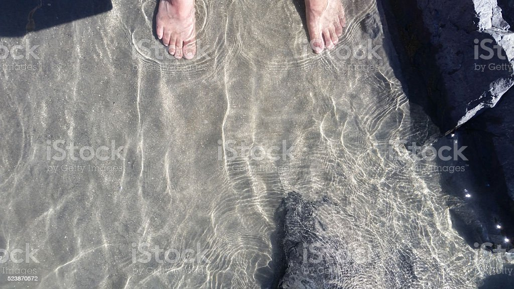 Standing on Sand in a Tide Pool stock photo