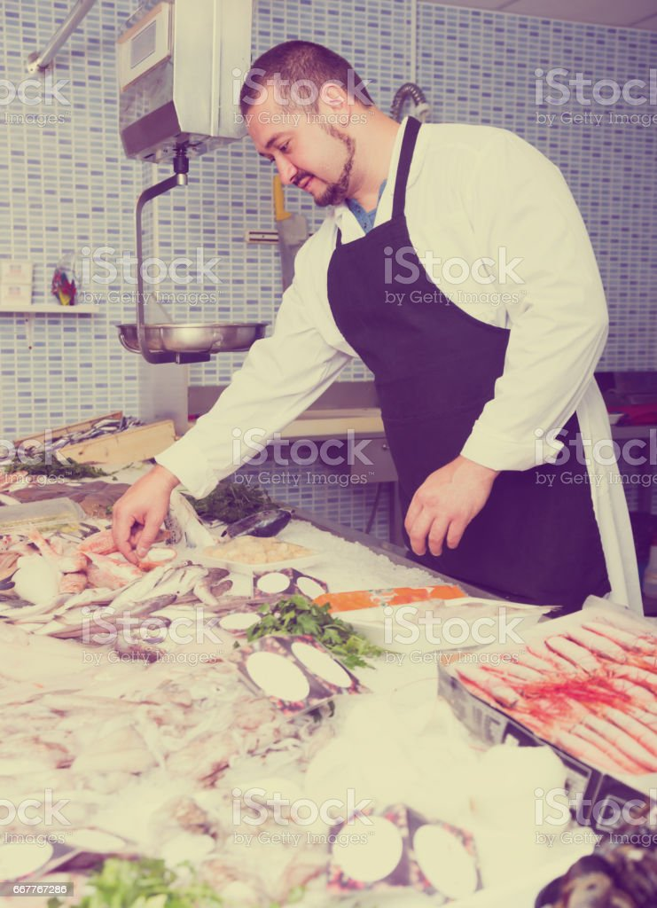 Standing smiling man shows the fish counter stock photo