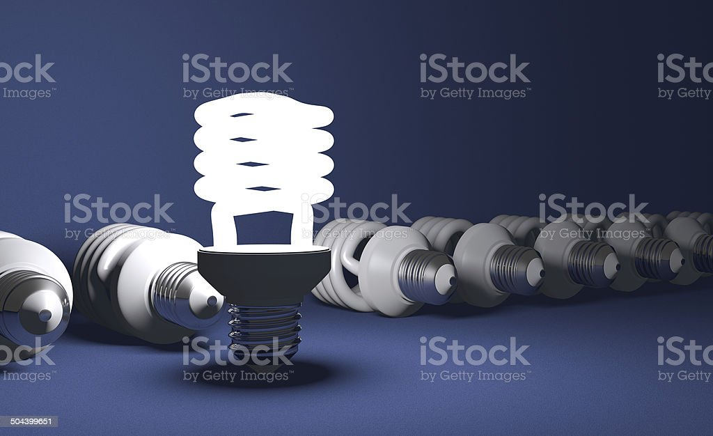 Standing spiral light bulb in row of lying ones royalty-free stock photo
