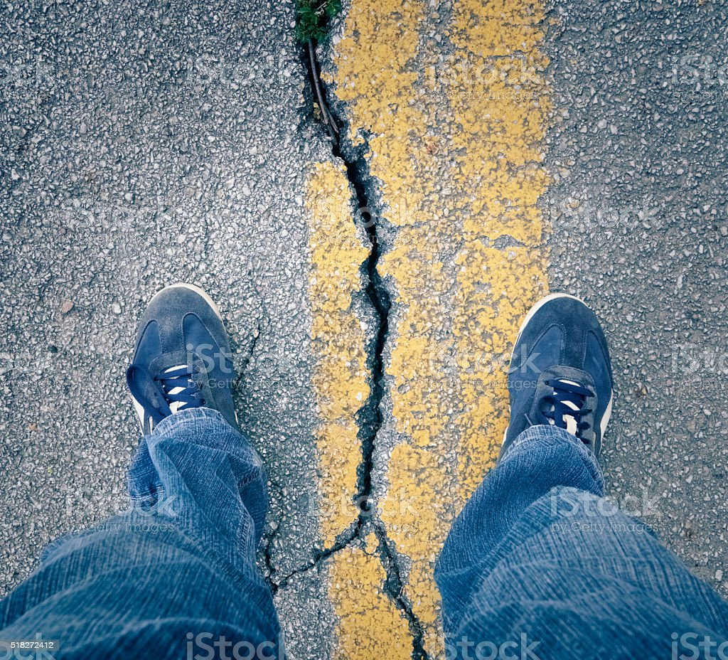 Standing with my feet across large crack in the asphalt stock photo