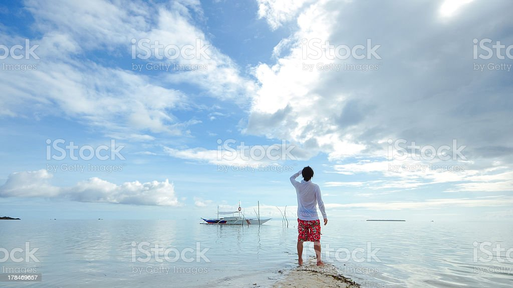 standing young man looks at horizon on beach royalty-free stock photo