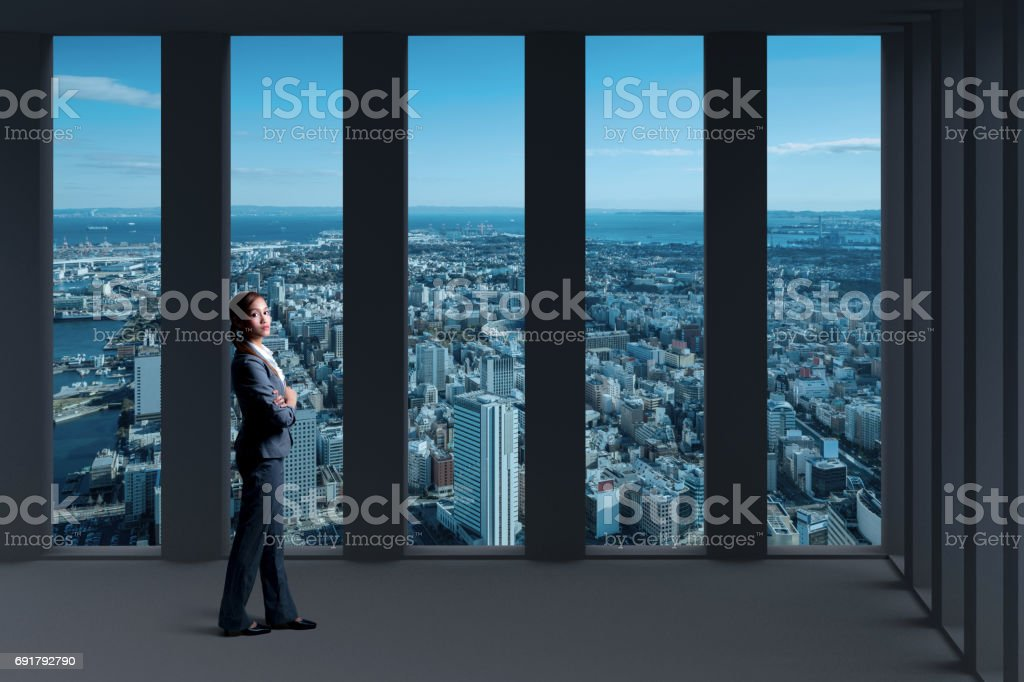 standing young woman and modern city panorama view from inside of building stock photo