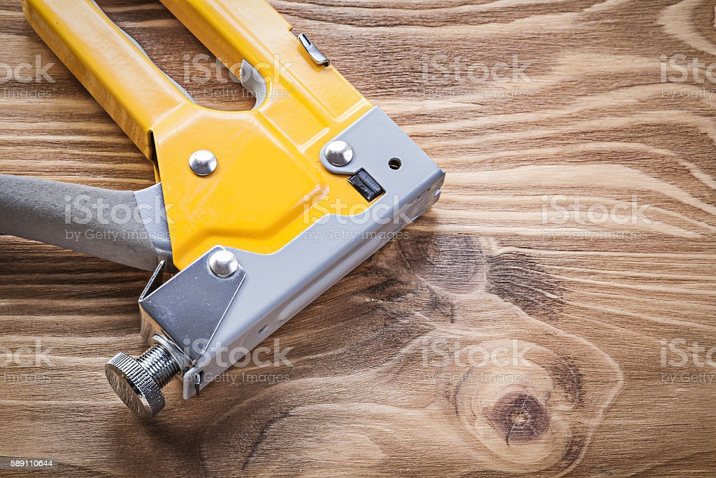 Staple gun on wooden board directly above construction concept stock photo