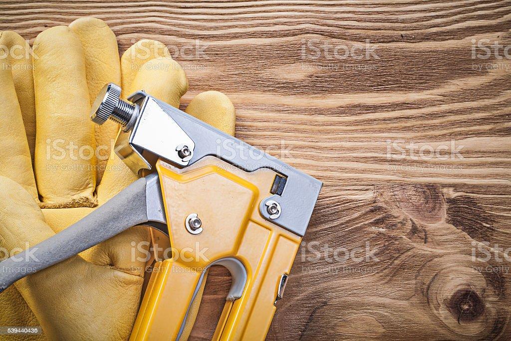 Staple gun protective gloves on wooden board construction concep stock photo