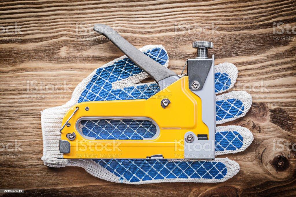 Stapler gun pair of working gloves on wooden board construction stock photo