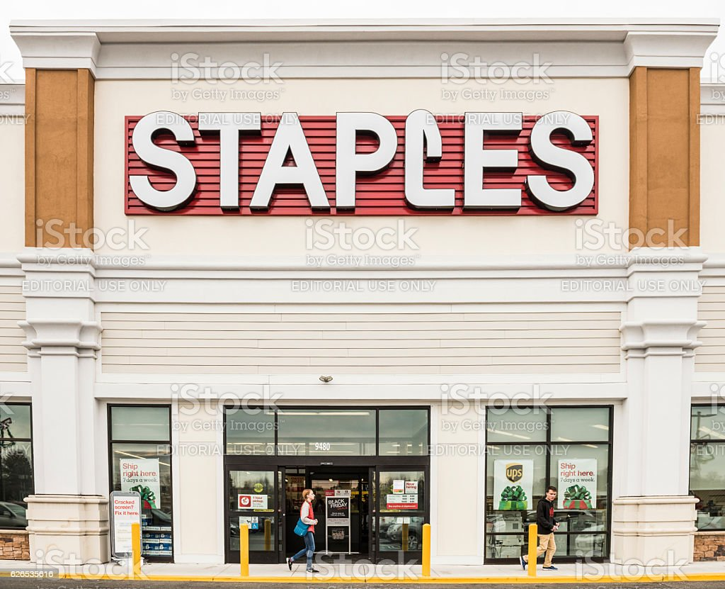 Staples store facade with large sign and person walking stock photo