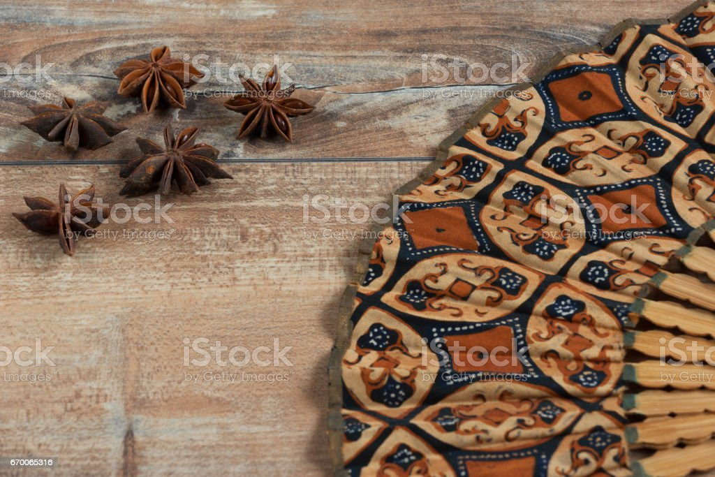 Star anise and fan on brown wooden background. stock photo