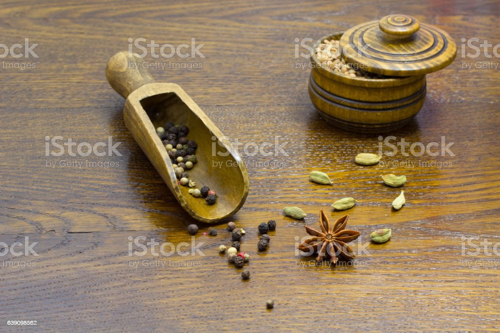 star anise cardamom on the table, pepper in  wooden spoon stock photo