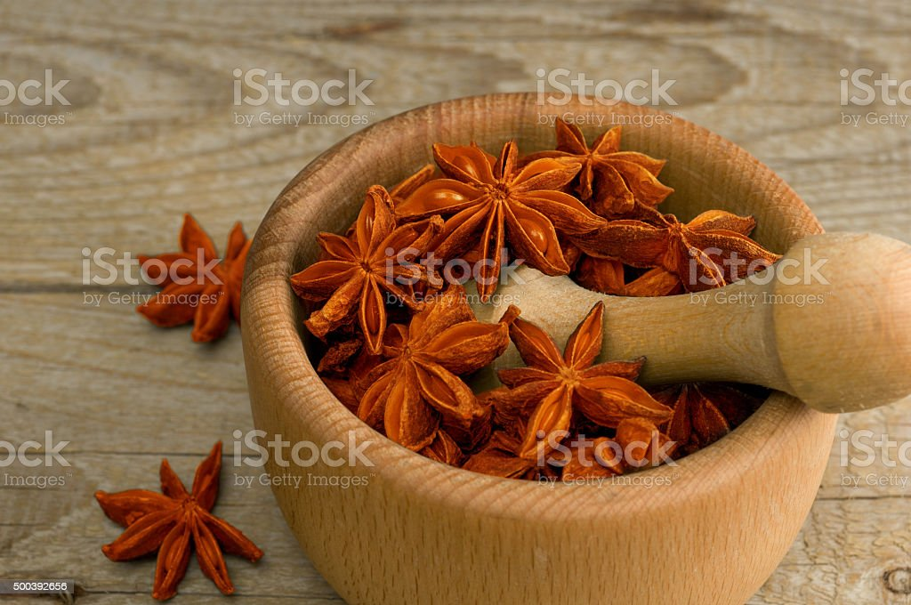 star anise in a wooden mortar stock photo