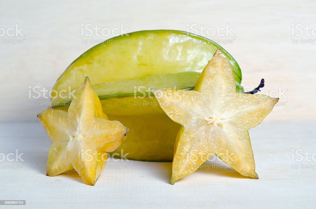 Star apple fruit with half cross section isolated on wooden stock photo