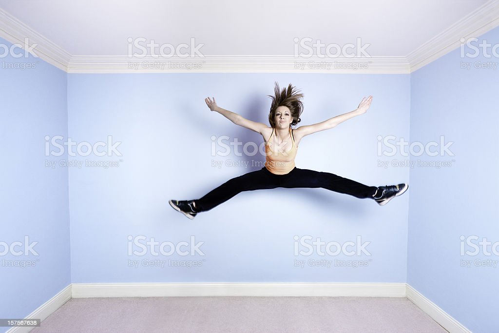 Star jump in blue room stock photo