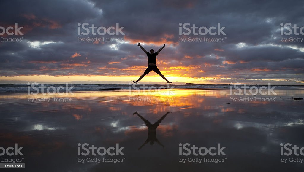 Star Jump on Beach with reflection stock photo