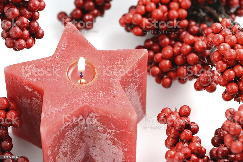 star shape Christmas candle with red fruits royalty-free stock photo