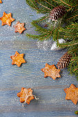 Star shaped ginger cookies and spruce branches with cones on