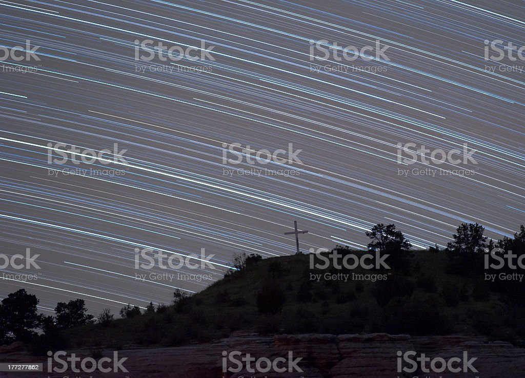 Star trails above cross on hill royalty-free stock photo