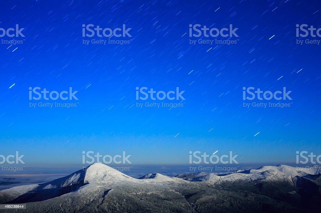 Star trails sur la chaîne de montagnes enneigées photo libre de droits
