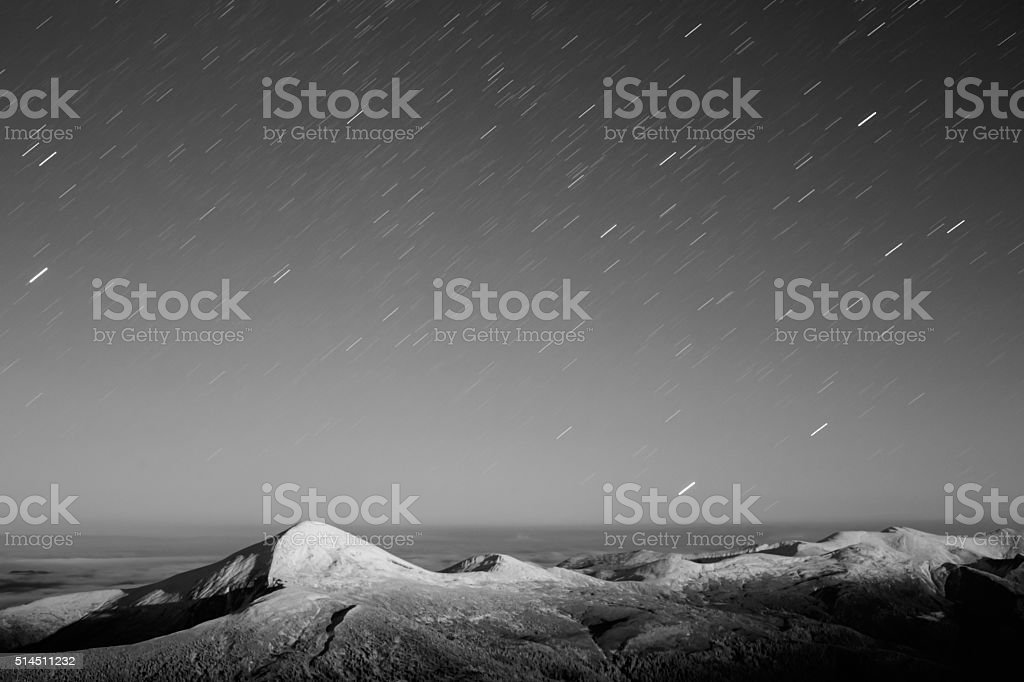 Star trails over the snowy mountain range stock photo
