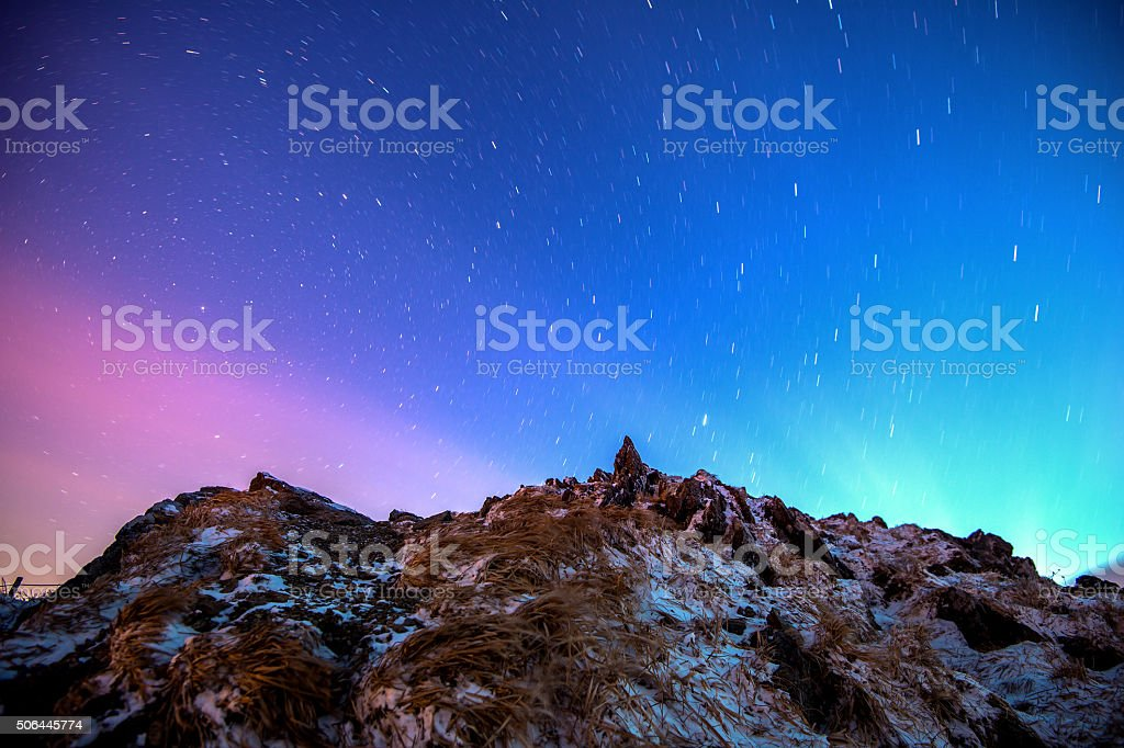 Star trails over the winter mountains landscape. stock photo