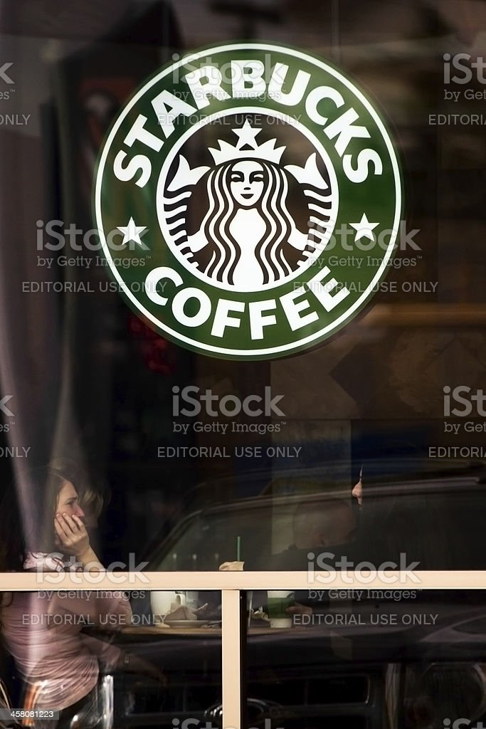 Starbucks logo in window with customers sitting inside royalty-free stock photo