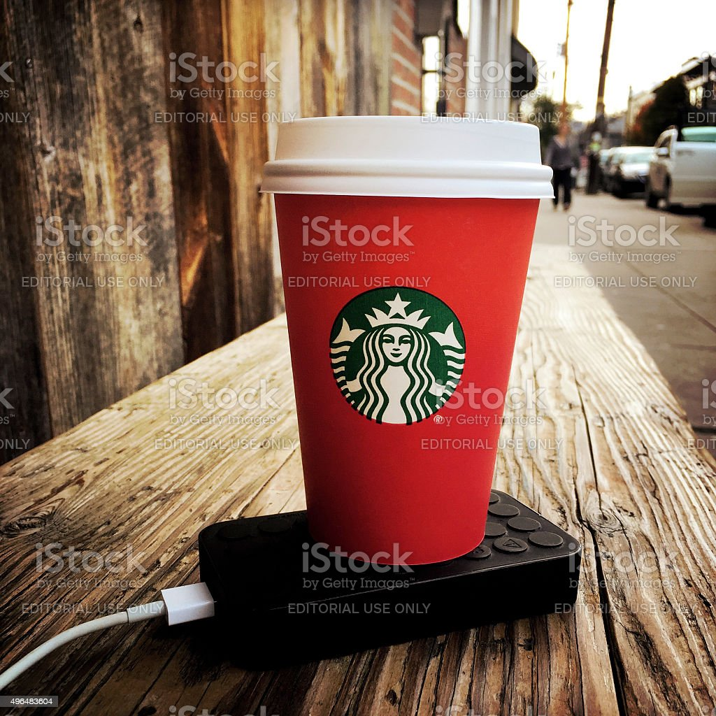 Starbucks Red Cup on Bench with Phone Charger stock photo