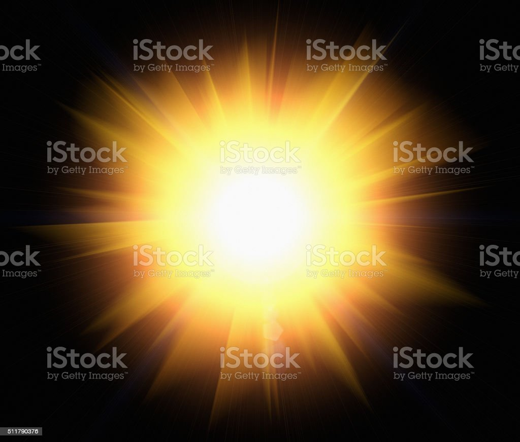 Starburst of bright golden light against black stock photo