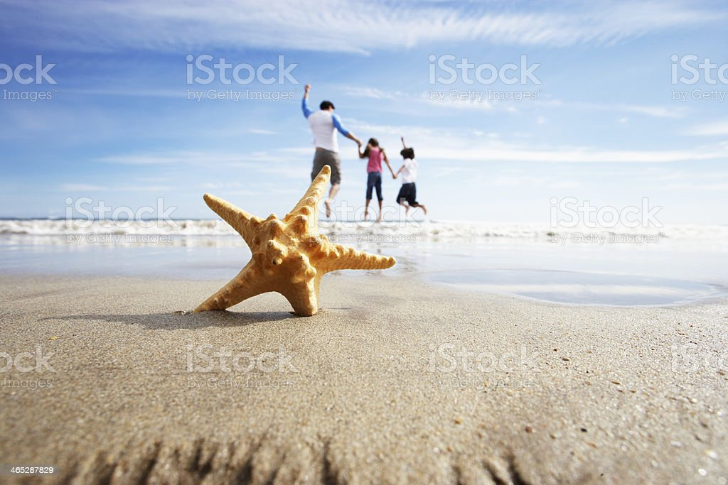 Starfish In Foreground As Father Plays With Children stock photo