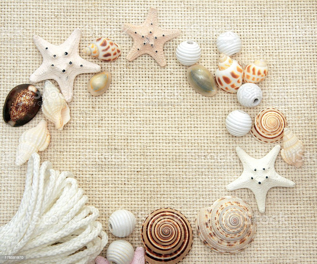 Starfishes and conches on canvas texture royalty-free stock photo