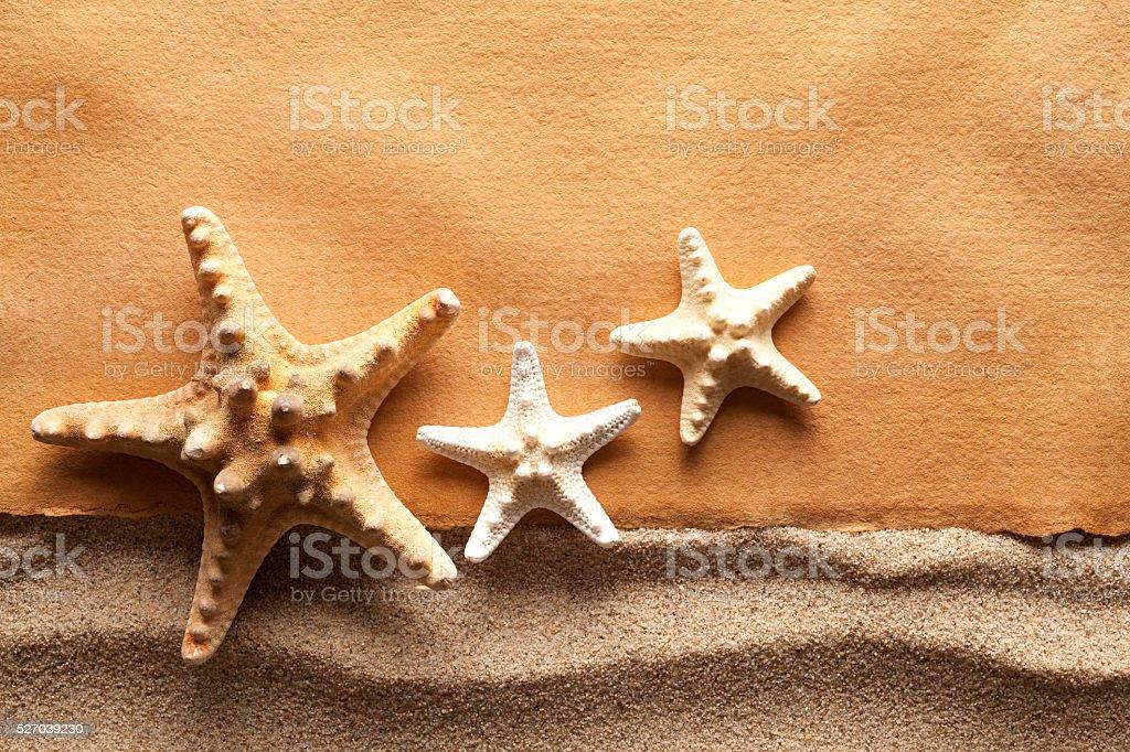 Starfishes and handmade paper sheet on beach stock photo