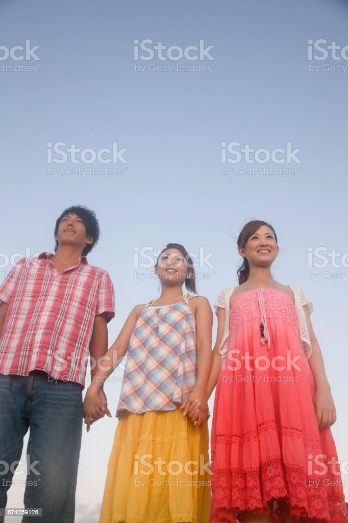 Staring into the distance, clearvale to men and 2 women stock photo