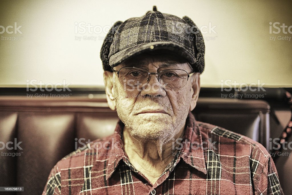 Staring Senior Man Wearing Plaid Hunter Cap stock photo