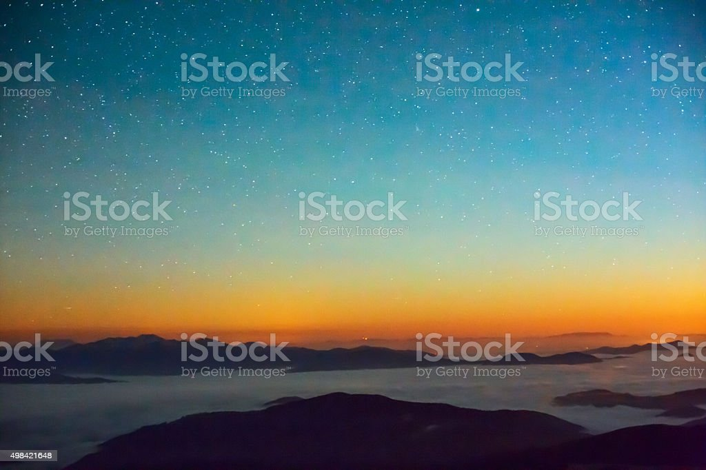 Starry night in cloudy mountains stock photo