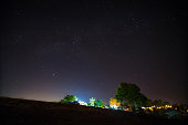 Starry night over tribe village on mountain.