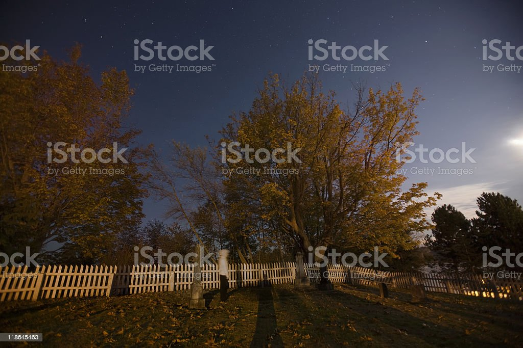 Starry Night Scary Cemetery with Fall Leaves stock photo