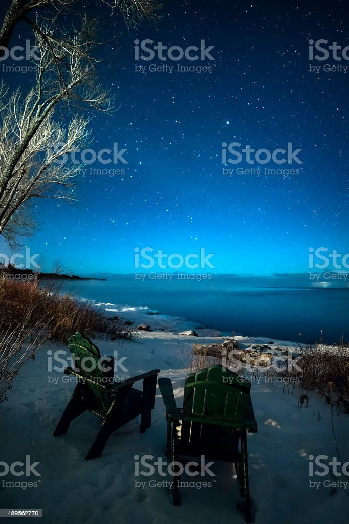 Starry skies above empty lawn chairs at lake stock photo