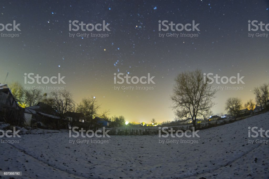 Starry sky above the village in the winter stock photo