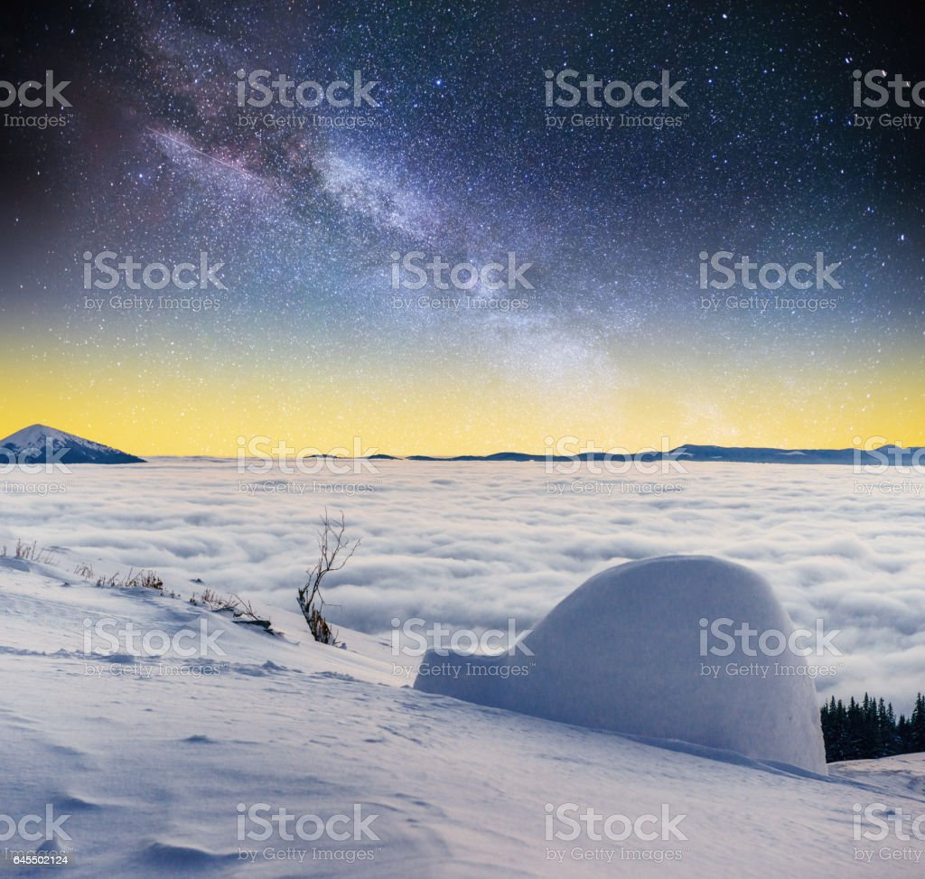 Starry sky and the Milky Way  a yurt in winter fog mountains stock photo