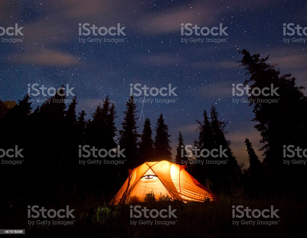 stars above the mountains with tent highlighted stock photo