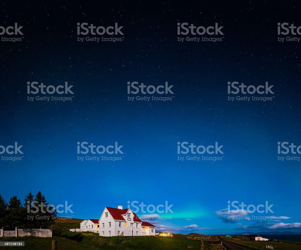 Stars and aurora shining over moonlit rural farm village Iceland stock photo