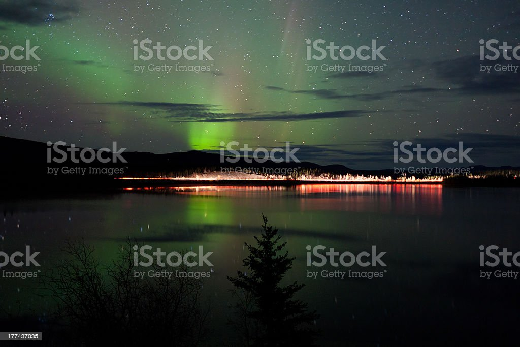 Stars and Northern Lights over dark Road at Lake royalty-free stock photo