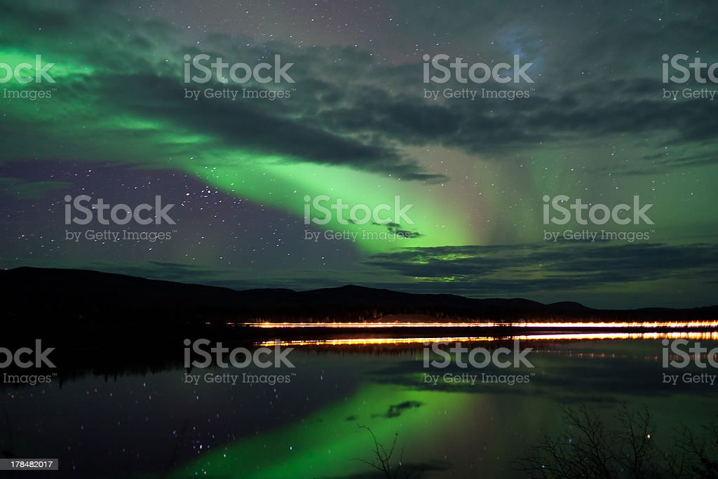 Stars and Northern Lights over dark Road at Lake stock photo
