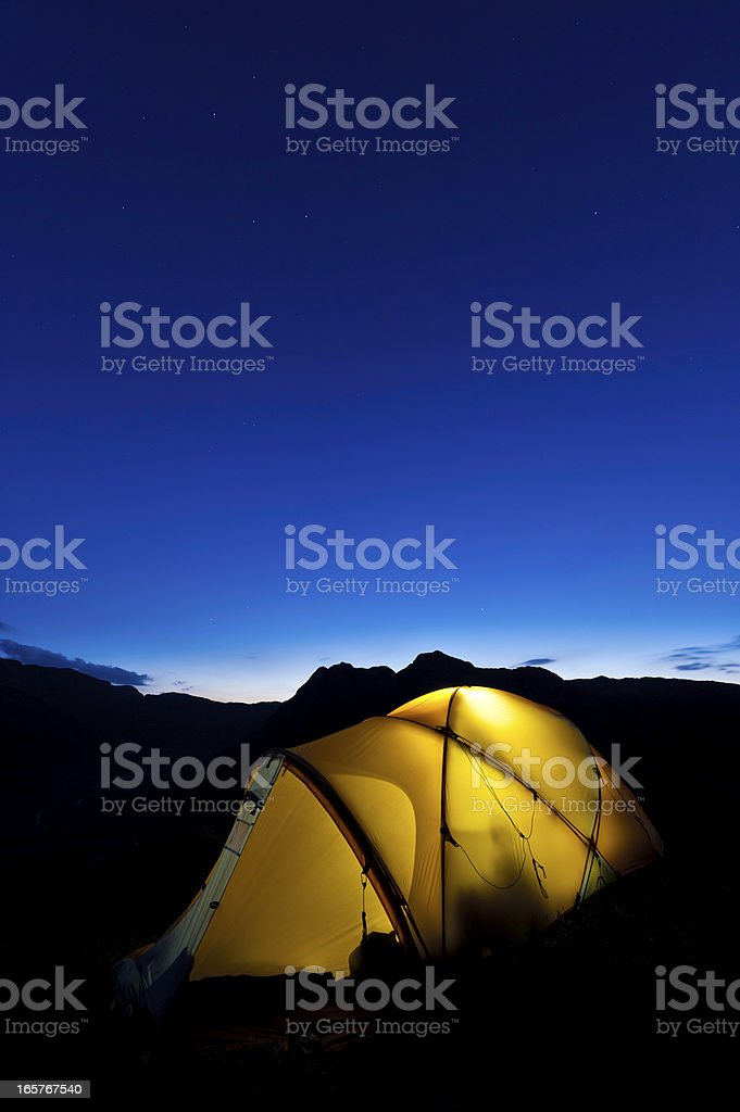 Stars shining above yellow dome tent mountain peaks royalty-free stock photo