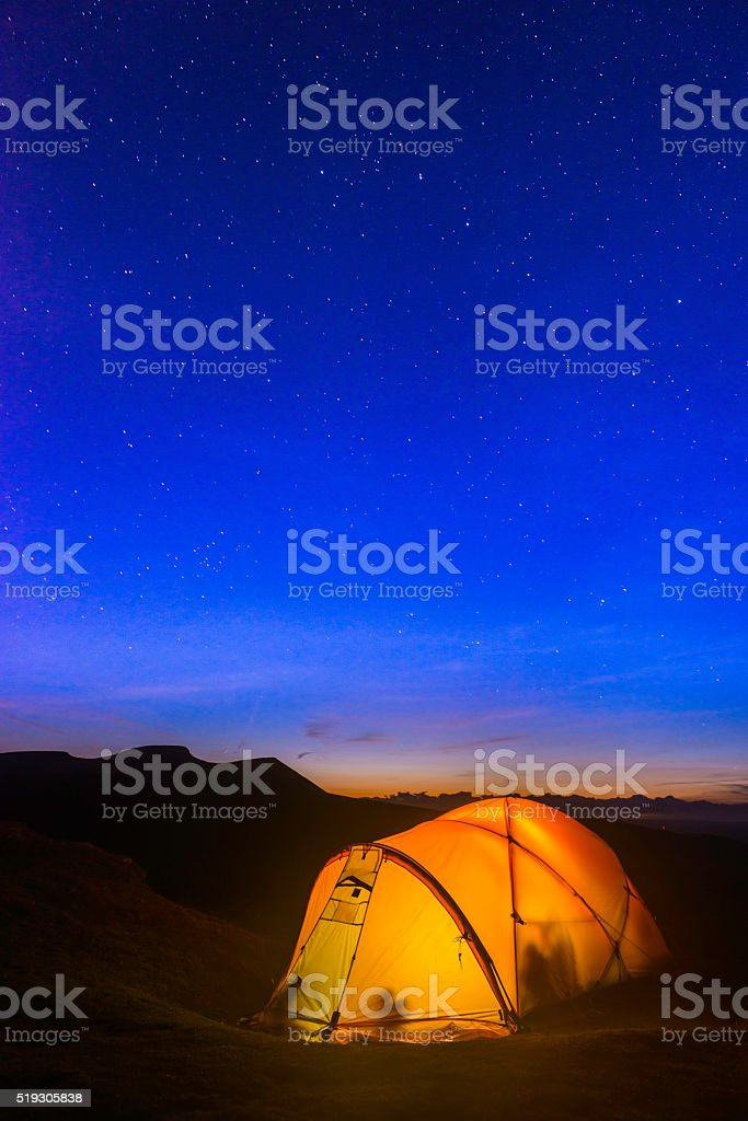 Stars shining in night sky above illuminated yellow mountain tent stock photo