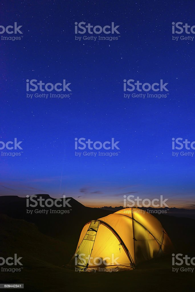 Stars shining over warm glowing tent and silhouetted mountain peaks stock photo