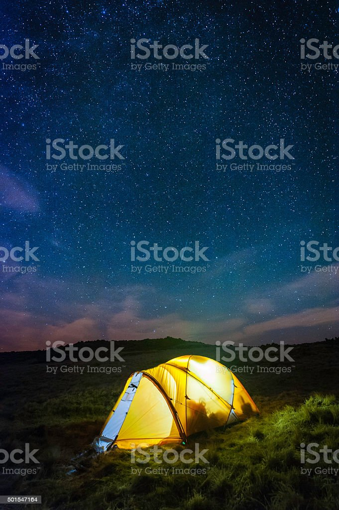 Stars shining over warmly glowing tent camping high on mountain stock photo