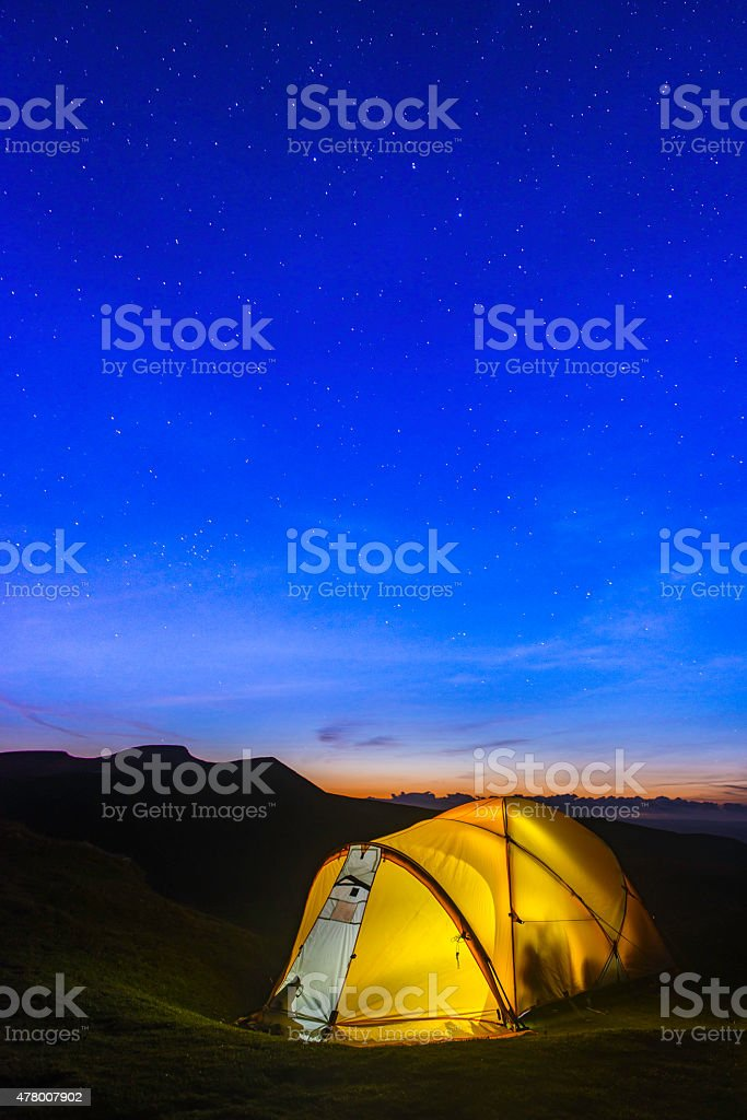 Stars shining over yellow dome tent illuminated in mountain camp stock photo
