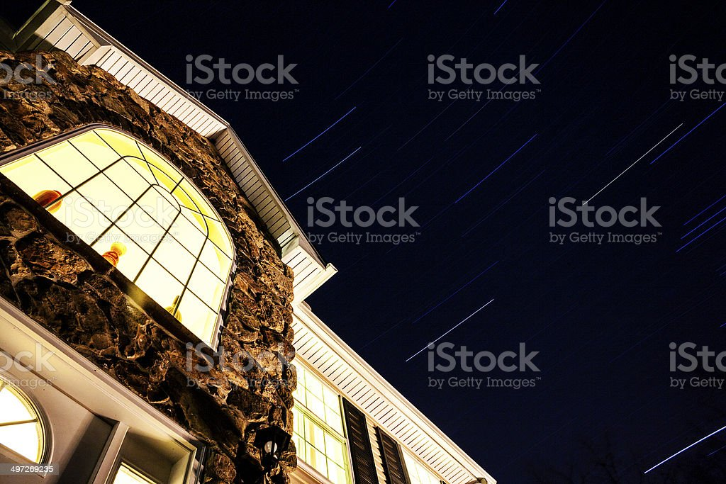 Stars trails on the sky above the living house royalty-free stock photo
