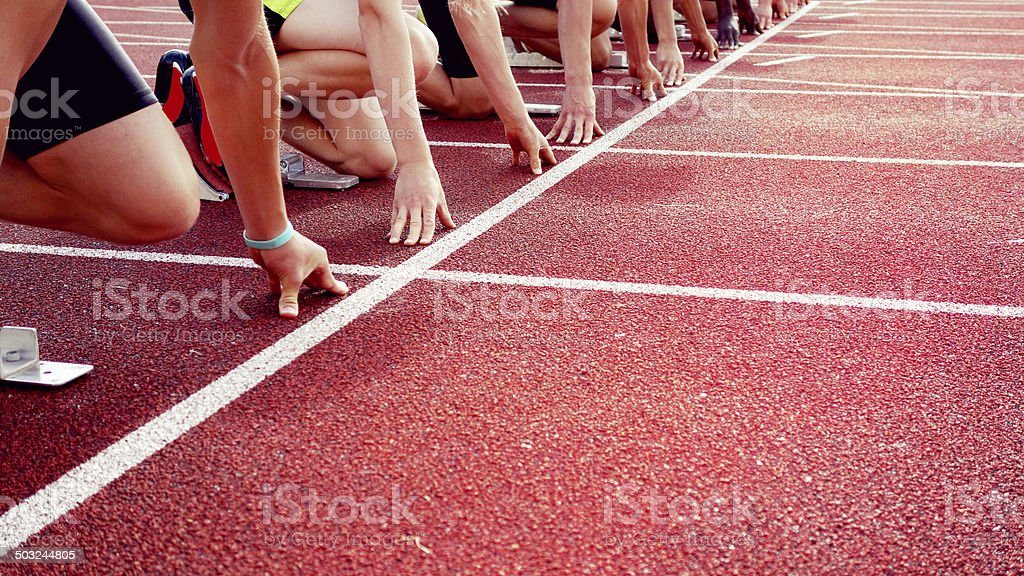 Young, athletic men at the start of a track event - unrecognizable...