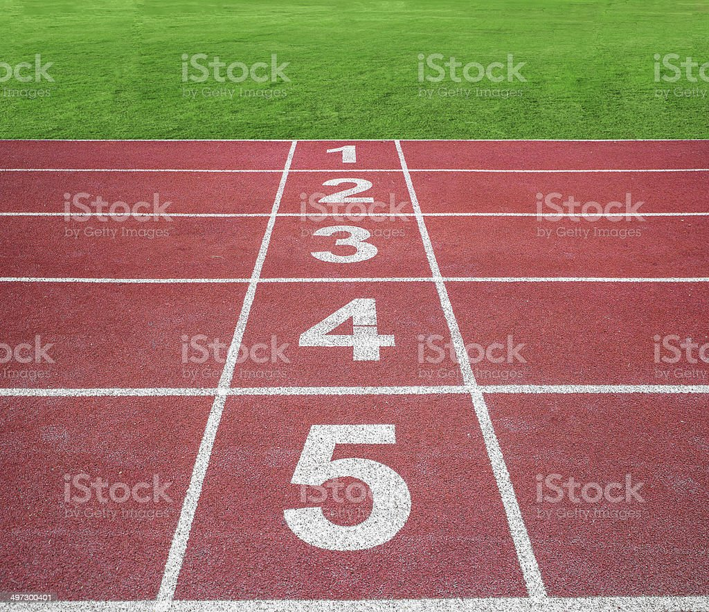 Start or finish position on running track with green field stock photo