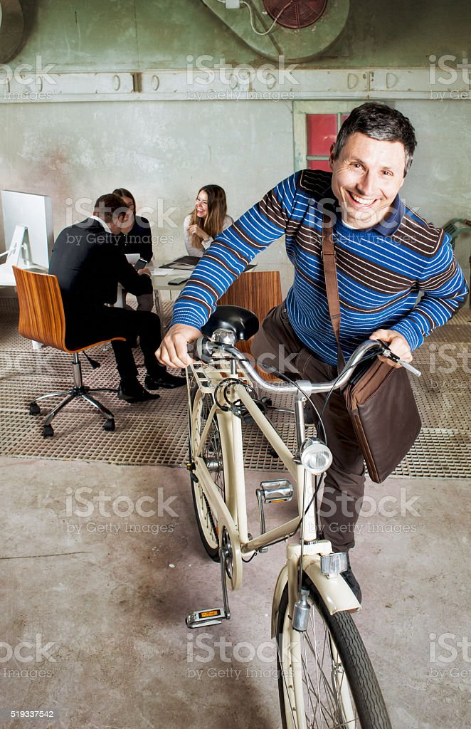 Start Up Company. Man Leaving Place of Work with Bicycle. stock photo