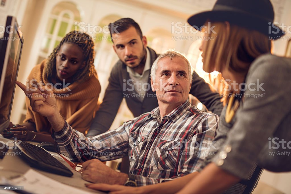 Start up team cooperating while working on desktop PC. stock photo